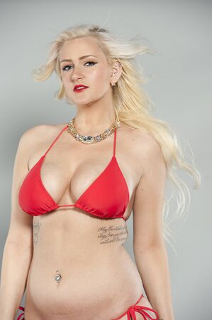 two piece swimsuit: Attractive young blond girl wearing a two piece red swimsuit in a studio with blue eyes.