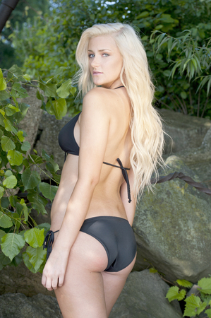 A beautiful young blond swimsuit model wearing a black swimsuit on a sunny day at the beach.
