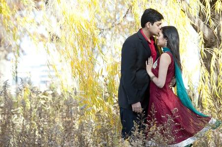 parejas romanticas: Un hombre indio joven que besa la frente de su novia india que está vestida con un sari y ambos están de pie bajo un árbol de sauce.