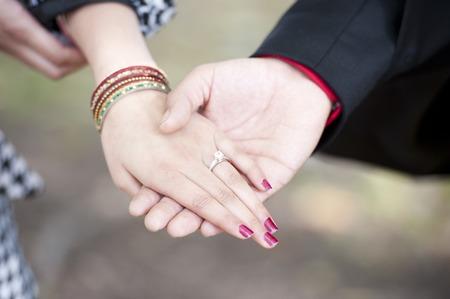 verlobt: Eine junge indische Paar Verlobung Hände an einem sonnigen Tag im Freien.