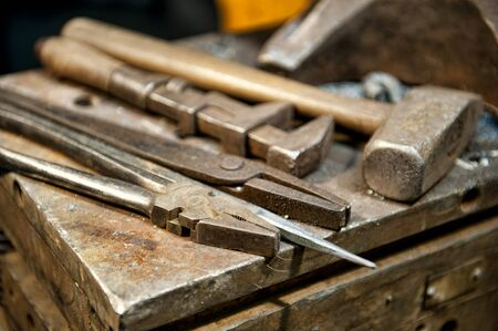 fabrication: A few metal crafting tools laying next to an anvil in a metal fabrication shop.