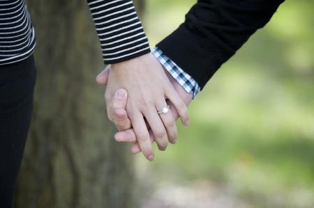 anillo de compromiso: Manos jovenes que se sostienen con un anillo de compromiso en un día soleado. Foto de archivo