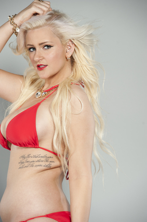 two piece: Attractive young blond girl wearing a two piece red swimsuit in a studio with blue eyes.