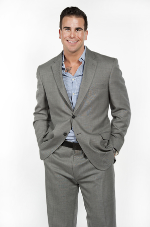 white suit: Athletic and attractive caucasian male wearing a fitted gray suit with a blue button down shirt in a studio setting on a white background posing and looking at the camera and smiling.