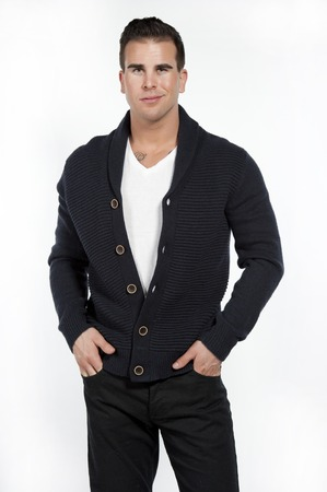 Good looking caucasian athletic male model wearing a trendy buttown down sweater, black pants and a white t-shirt posing in a studio on a white background while looking at the camera with his hands in his pockets.