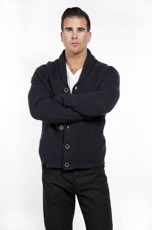 pantalones abajo: Buen modelo mirando caucásica atlético masculino llevaba un buttown abajo suéter de moda, los pantalones negros y una camiseta blanca posando en un estudio sobre un fondo blanco mientras mira a la cámara con las manos cruzadas.