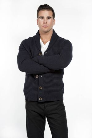 pants down: Good looking caucasian athletic male model wearing a trendy buttown down sweater, black pants and a white t-shirt posing in a studio on a white background while looking at the camera with his hands crossed.