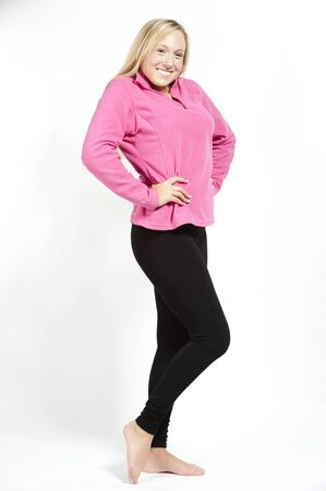black pants: A happy young attractive female model wearing a pink sweatshirt with black pants on a white background.