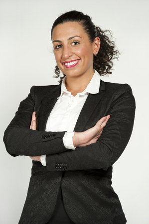 to the secretary: A happy gorgeous young brunetee lawyer secretary with curly hair up in a bun and wearing a black suit on a white background while looking at the camera.