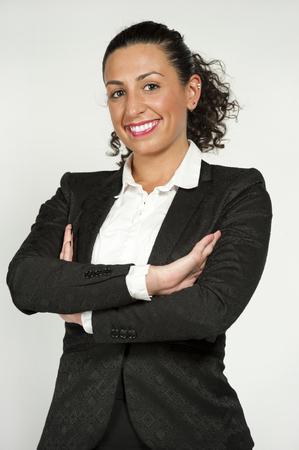 SECRETARIA: Una hermosa joven brunetee secretario abogado feliz con rizado el pelo en un mo�o y llevaba un traje negro sobre un fondo blanco mientras mira a la c�mara.