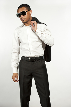 pants down: A young chic black male wearing sunglasses, white button down shirt with black pants with sports jacket over his shoulder in a studio setting on a white background.
