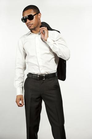 pantalones abajo: Un joven elegante hombre negro con gafas de sol, bot�n abajo camisa blanca con pantal�n negro con chaqueta deportiva sobre su hombro en una configuraci�n en un fondo blanco del estudio.