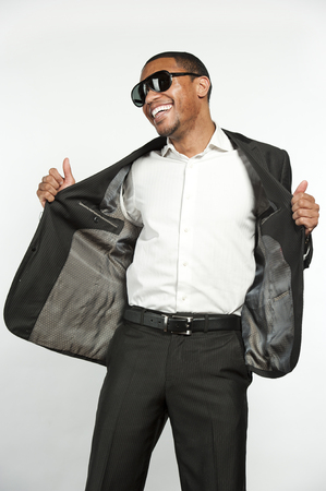button down shirt: A young happy black male wearing sunglasses, white button down shirt with a custom suit jacket being playful in a studio setting on a white background.