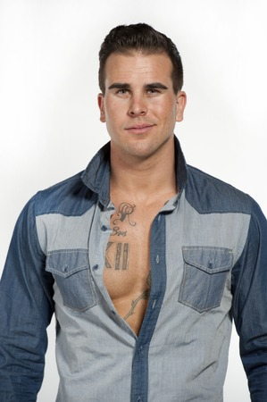 smirking: Attractive white caucasian male model smirking wearing a jean shirt posing in a studio on a white background while looking at the camera.
