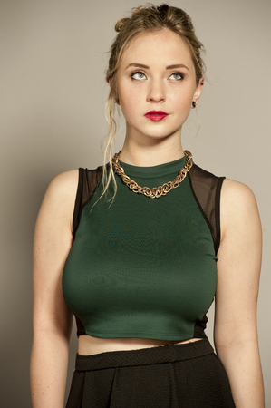 busty: Beautiful busty young female brunette with straightened hair in a studio setting while wearing a green top and a short black mini skirt on a gray background.