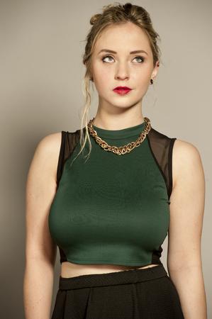 mini skirt: Belle jeune femme brune plantureuse femme avec des cheveux redress� dans un studio tout en portant un haut vert et une mini jupe courte noire sur un fond gris.
