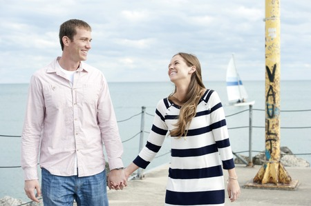 love couple: A young happy caucasian couple on a sunny day with the clouds in the background at the pier. Stock Photo