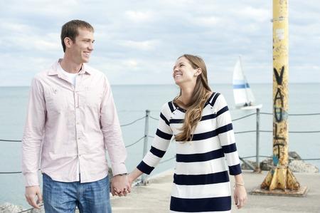 couple  amoureux: Un jeune couple caucasien heureux sur une journ�e ensoleill�e avec des nuages ??en arri�re-plan � l'embarcad�re.
