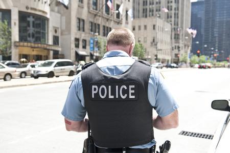 証拠晴れた日に弾丸を着て道路に立っているシカゴ市の警官は、彼の体に警察を言及するベストします。背景には、車と高層ビルを見られます。 写真素材