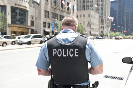 uniforms: A Chicago city policeman standing on the road on a sunny day wearing a bullet proof vest mentioning Police on his body. On the background, cars and tall buildings are seen.