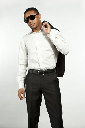 button down shirt: A young chic black male wearing sunglasses, white button down shirt with black pants with sports jacket over his shoulder in a studio setting on a white background.