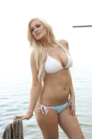 Young blonde girl wearing a two piece white swimsuit at the beach.