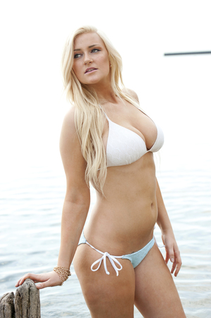 busty: A young gorgeous busty blonde wearing a two piece white swimsuit.