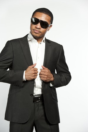 button down shirt: A young vogue style black male wearing sunglasses, white button down shirt with a custom suit jacket in a studio setting on a white background. Stock Photo