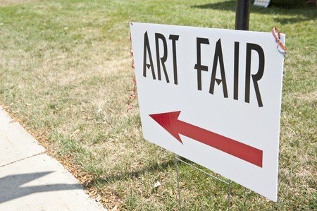 capitalized: A sign that says ART FAIR with a red arrow pointing left. Stock Photo