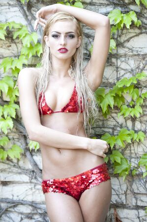 traje de bano: Preciosa chica rubia joven que llevaba un traje de ba�o de dos piezas de color rojo brillante que mira a la c�mara mientras posando sobre un fondo de la vid al aire libre en un d�a soleado. Foto de archivo