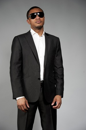 An attractive African American male wearing a custom suit with sunglasses posing in a studio setting on a gray background. Foto de archivo