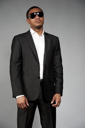 traje: Un atractivo hombre afroamericano vestido con un traje a medida con gafas de sol posando en un ambiente de estudio sobre un fondo gris. Foto de archivo