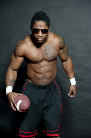 african american nude: Attractive African American football player posing shirtless with black shorts and sunglasses while holding a football in his right hand in a studio setting on a black background.