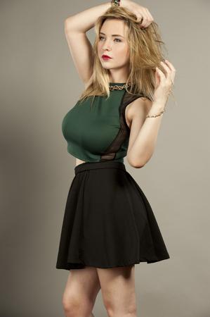 mini jupe: Belle jeune femme brune plantureuse femme avec des cheveux redressé dans un studio tout en portant un haut vert et une mini jupe courte noire sur un fond gris.