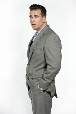 button down shirt: Athletic and attractive caucasian male wearing a fitted gray suit with a blue button down shirt in a studio setting on a white background posing and looking at the camera.