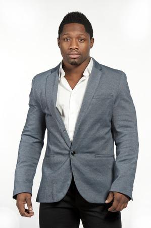 카메라를 찾고있는 동안 흰색 배경에 스튜디오에서 포즈에서 셔츠와 회색 장착 양복을 입고 매력적인 흑인 남성 모델.