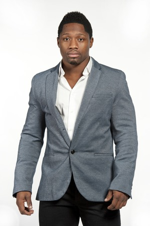 Attractive African American male model wearing a gray fitted suit with a shirt under posing in a studio on a white background while looking at the camera.