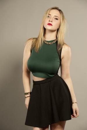 녹색 상단과 회색 배경에 짧은 검은 미니 스커트를 입고 스튜디오 설정에서 곧은 머리를 가진 아름다운 가슴 젊은 여성 갈색 머리.