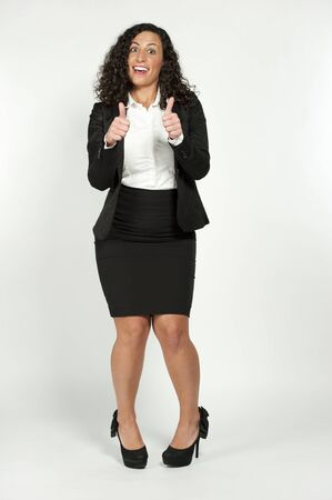 corporate women: Funny beautiful young brunette showing thumbs up while wearing a white shirt with a black suit jacket on a white background.