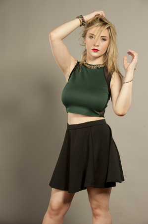 Beautiful busty young female brunette with straightened hair in a studio setting while wearing a green top and a short black mini skirt on a gray background.