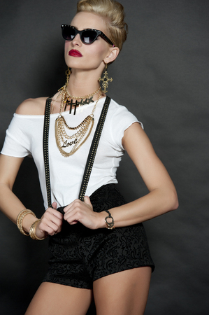 gorgeous woman: Gorgeous young female blonde wearing a white top, trendy black shorts with suspenders, gold necklace and earings with crosses, and hip sunglasses on a back background in a studio. Stock Photo