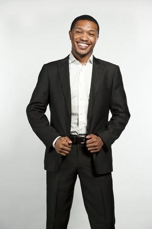 traje formal: Un joven elegante hombre negro que ríe mientras llevaba camisa blanca con botones con una chaqueta de traje a medida en una configuración en un fondo blanco del estudio.