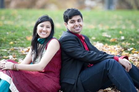 Un joven y feliz pareja india que se sienta en las hojas espalda con espalda en el otoño en un día nublado. Foto de archivo - 48478996