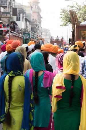 Several local Sikh people including both men and women gathering to offer prayer in front of a religious march in Delhi. On the background, the religious ceremony is seen.