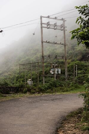 routing: An electric pole carrying high voltage on the roadside whilst routing up the Nilgiri hills in Kochi, Kerala. On the background, the hillscape and foggy sky view is seen. Stock Photo