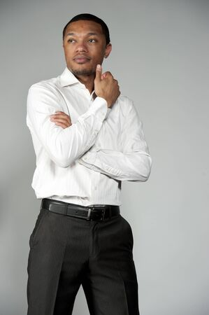 slacks: An attractive African American boy wearing a white button down and black slacks on a gray background in a studio setting.