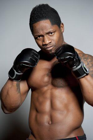 seins nus: Attractive African American male body builder posant dans un décor de studio sur un fond gris dans une posture de boxe tout en torse nu portant un short noir et des gants de boxe.