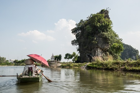 paddler: Paddler paddling a boat with tourists on the Ngo Dong river while touring Tam Coc caves in Hoa Lu. On the background, limestone karsts and ancient Tam Coc temple is seen.