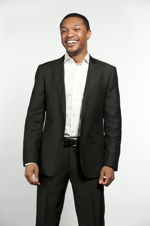 button down shirt: A young chic black male laughing while wearing white button down shirt with a custom suit jacket in a studio setting on a white background.