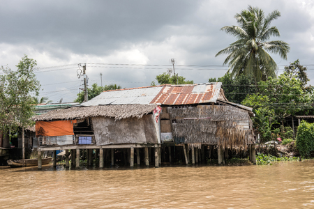 residences: Riverside residences on the Mekong river in Cai Be river-land town of Mekong delta region in Vietnam. Clothes are seen hanging on ropes in the houses. A Boat is also seen on the picture.